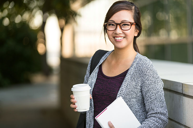 young asian female glasses smiling outdoors