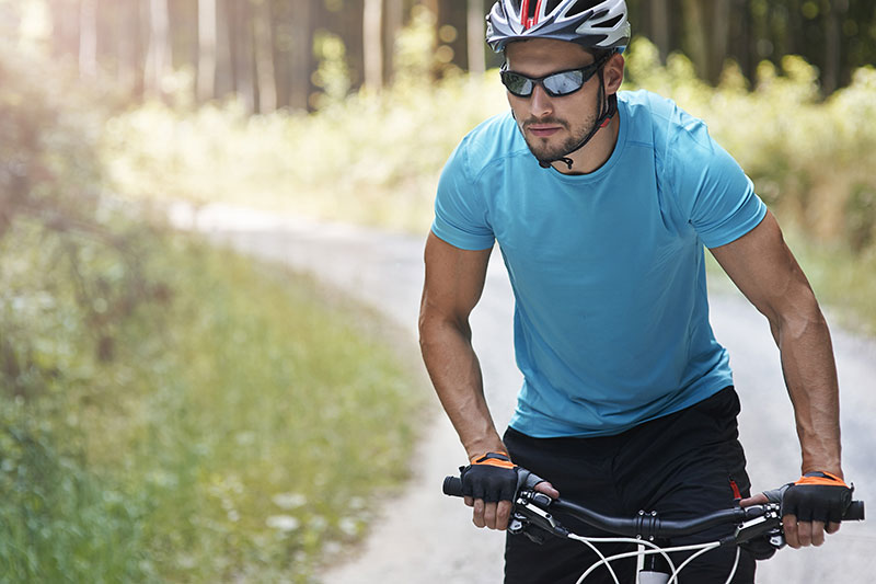 white male riding bicycle wearing sunglasses