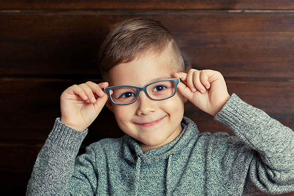 Youth boy pediatric holding eyeglasses